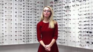 woman standing in front of rack of eyeglasses